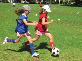 Children playing soccer, soccer camp, girls soccer